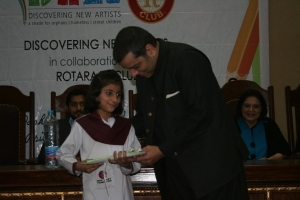 "PTI MPA Murad Rass awards a book to a student from Hope Uplift Foundation during the prize distribution ceremony of ""Jeet Key Perhao"" Creative Writing Competition at Forman Christian College on Friday, December 6th, 2013 in Lahore, Pakistan.  About 15 students were declared winners out of which 12 were awarded handsome scholarships. Course books, story books and uniforms were also a part of the prizes."