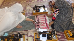 Sewing trainer teaching a participant how to cut a piece of cloth