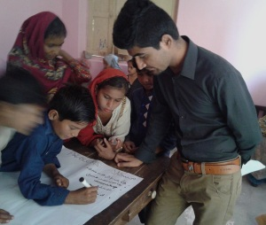 UGrad Alumnus Sarwan Kumar conducting an activity with students of Government Boys Primary School Parha Colony Mithi, in which they are writing down the problems faced by the residents of Tharparkar