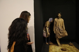 "Two female visitors look on as performance artists present their exhibit 'Rang-e-Khaak' at ""We Are All Mad Here"" exhibition"